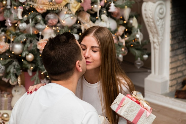 Couple kissing with gift in front of christmas tree