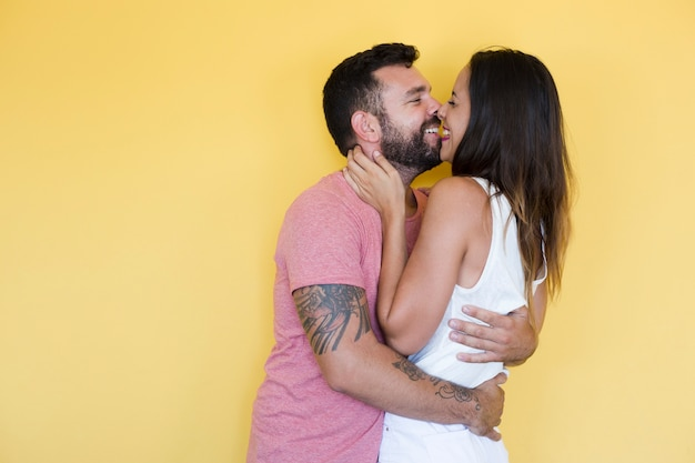Couple kissing on yellow background