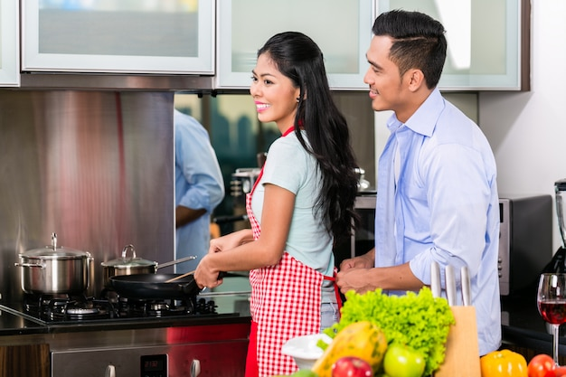Couple in kitchen cooking food