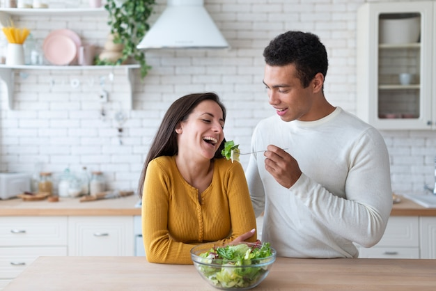 Couple in kitchen eating salad