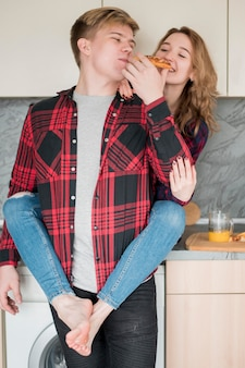 Couple in kitchen eating