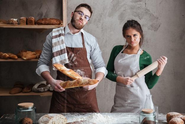 Couple at kitchen looking seriuosly at camera