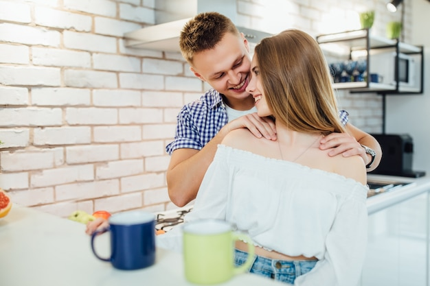 Of couple in the kitchen, man doing massage for his woman.