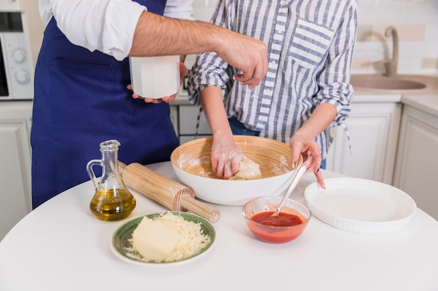 Couple kneading dough for pizza in bowl