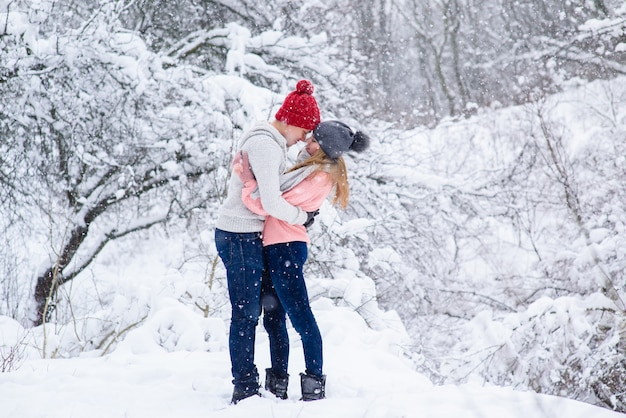 Couple in knitted hats going to kiss