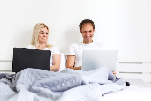 Couple on laptop in bed working on separate computers. young modern interracial couple, woman, caucasian man, view with copy space.