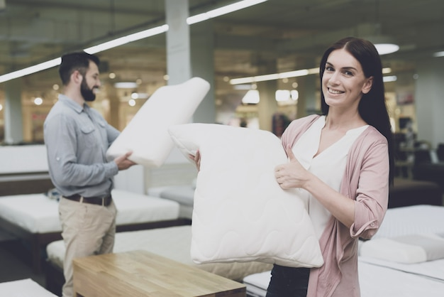 Couple in large store of beds chooses pillows.