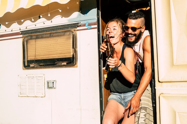 커플은 많이 웃고 야외 대안 방황 tmillennial 여름 휴가 휴가를위한 오래된 복고풍 캠핑 캐러밴의 문에 관계와 우정에서 함께 재미를