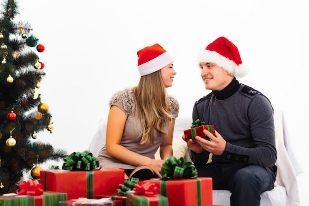 Пара смеется и обменивается подарками, на переднем плане гора красных и зеленых подарков