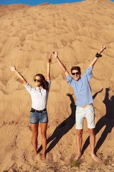 Пара смеется и играет на пляже