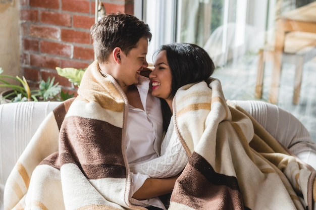 Couple laughing covered with a blanket