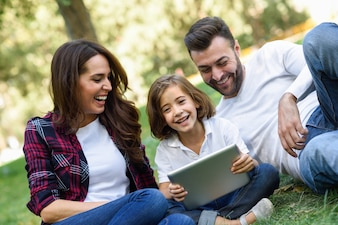 Couple laughing with their daughter and a laptop