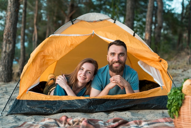 Couple laying down in the tent looking at camera