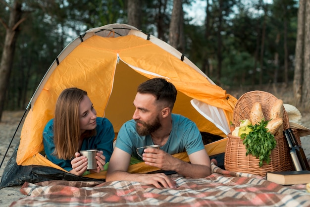 Couple laying down in the tent looking at each other