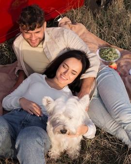 Пара, лежа на траве высоким углом