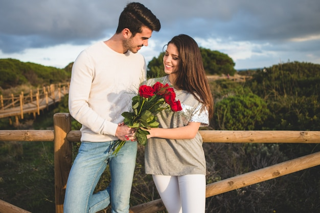 Couple leaning on a railing of a bridge with a bouquet of roses