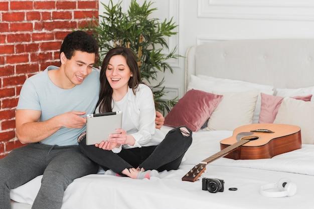 カップルが一緒にギターを弾く方法を学ぶ