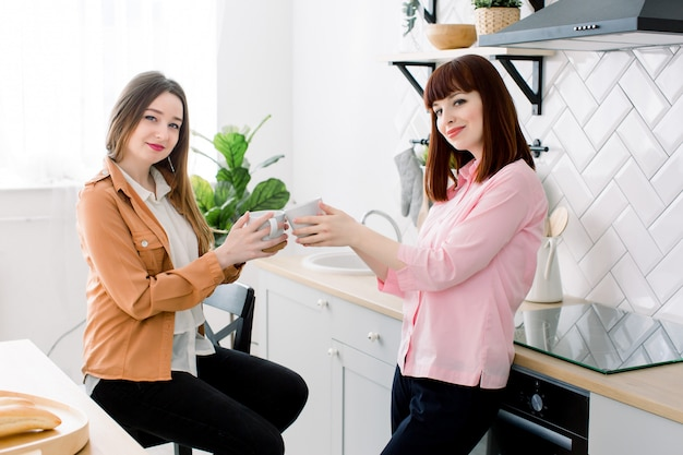 Couple of lesbian girls enjoy coffee at home taking about something. two young adult beautiful women drink tea in modern kitchen white interior