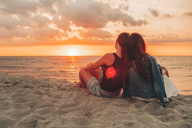 Couple of lesbian girls sitting on the beach and watching and enjoying a beautiful sunset together. summer time, vacation, lgbt.