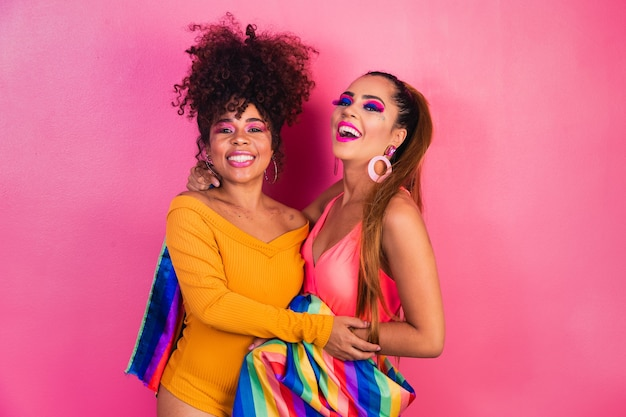 Пара лесбиянок с флагом гей-прайда на желтом фоне