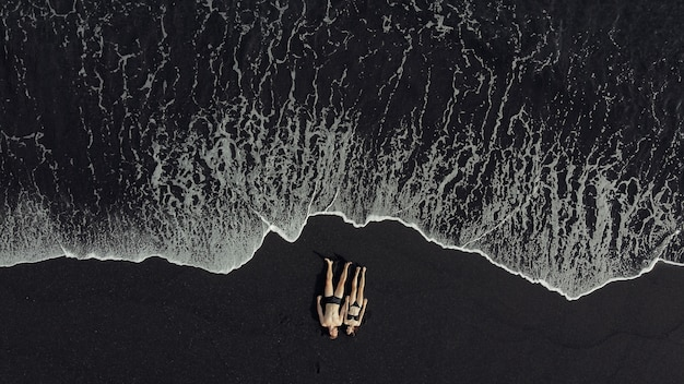 Couple lie on a black sand near ocean