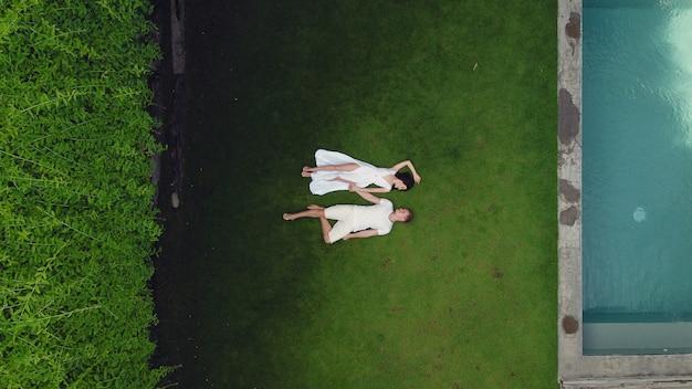 カップルはバリ島の草の上にあります。