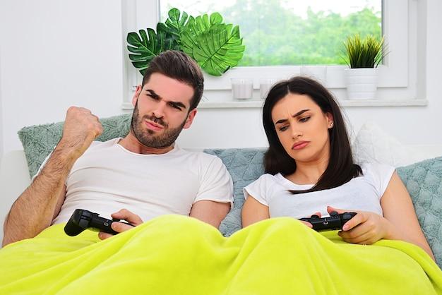 부부 생활, 승패, 파트너 개념 간의 경쟁. 젊은 부부는 소파에 비디오 게임