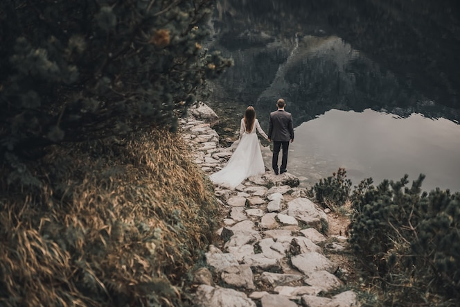 Couple of light-skinned newlyweds in wedding clothes. a large transparent lake and gray stones and trees