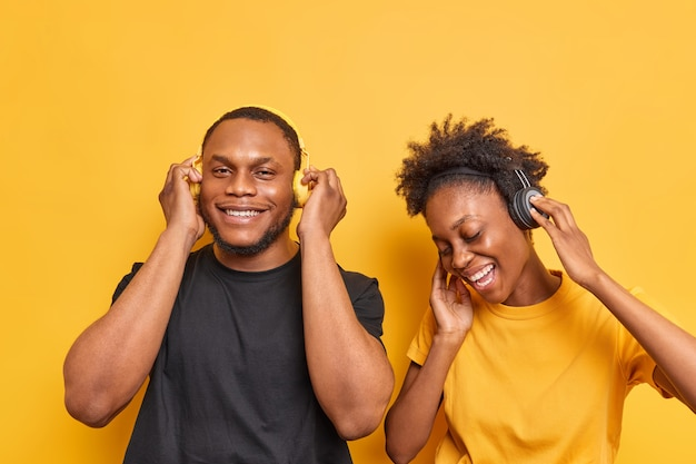 La coppia ascolta la musica canta la canzone preferita e si gode il tempo libero vestita casualmente isolata su un giallo vivido