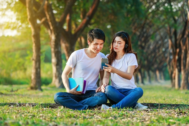 Couple listening music from mobile with headphone in the park