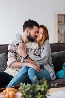 Couple in living room hugging front view