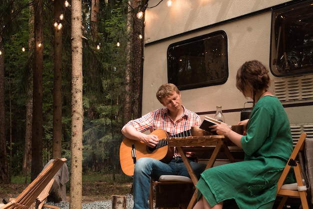 Couple living in trailer in summer vacation having a breakfast outdoor