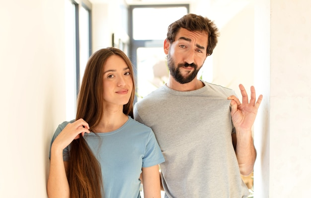 Couple looking arrogant, successful, positive and proud, pointing to self
