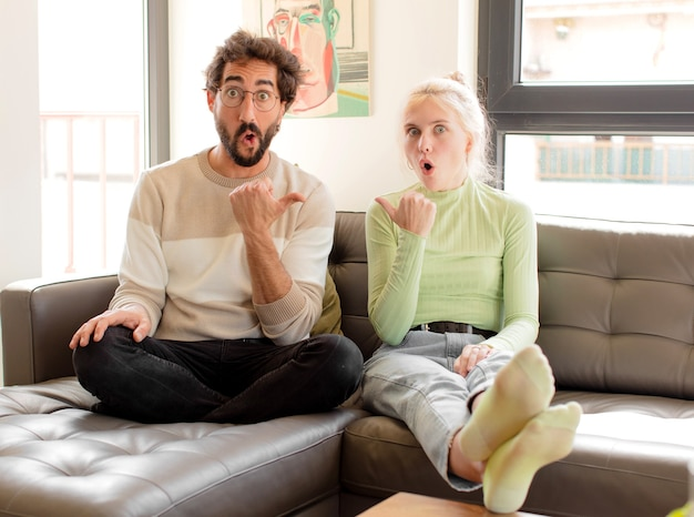 Couple  looking astonished in disbelief, pointing at object on the side and saying wow, unbelievable