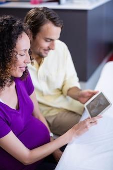 デジタルタブレットで赤ちゃん超音波スキャンを見てカップル