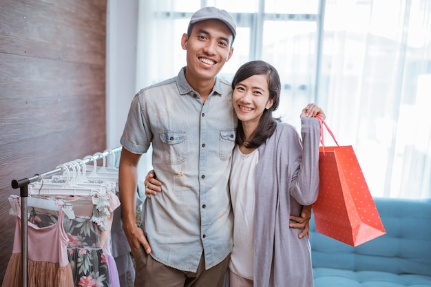 Пара смотрит в камеру, держа бумажный пакет в небольшом бутике