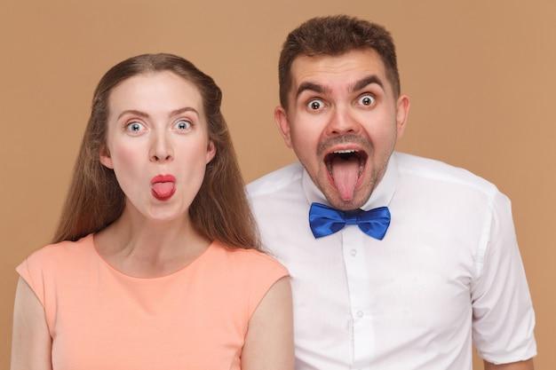 Пара смотрит в камеру с удивленными большими глазами и высунутым языком