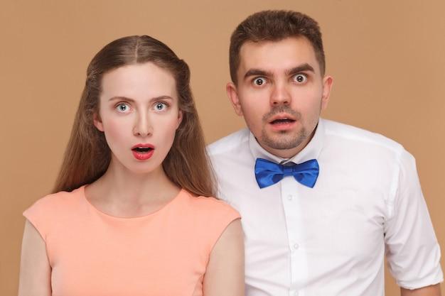 Пара смотрит в камеру с удивленным лицом и большими глазами