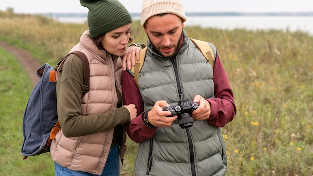 自然の中でデジタルカメラを見ているカップル