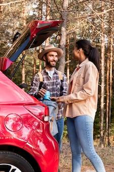 車からバックパックを取得しながらお互いを見ているカップル