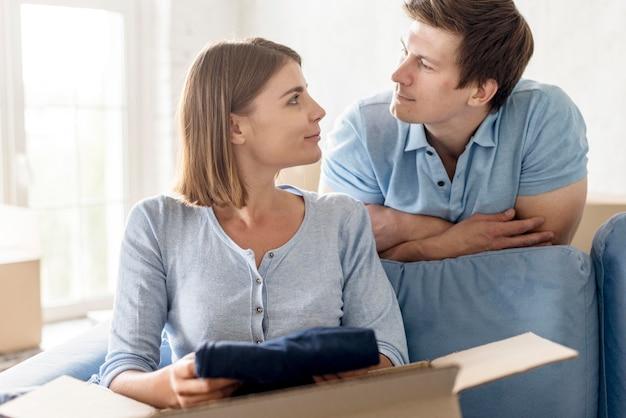Пара смотрит друг на друга, упаковывая коробку, чтобы переехать
