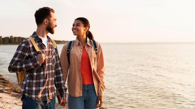 海の横を散歩しながらお互いを見つめるカップル
