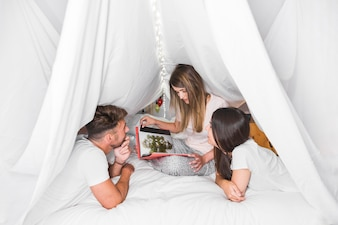 Couple looking at her friend looking photo album under the curtain on bed