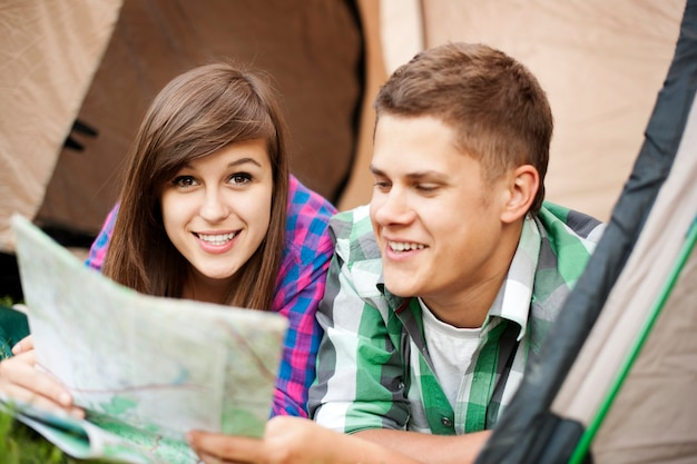 テントの中で地図を見ているカップル