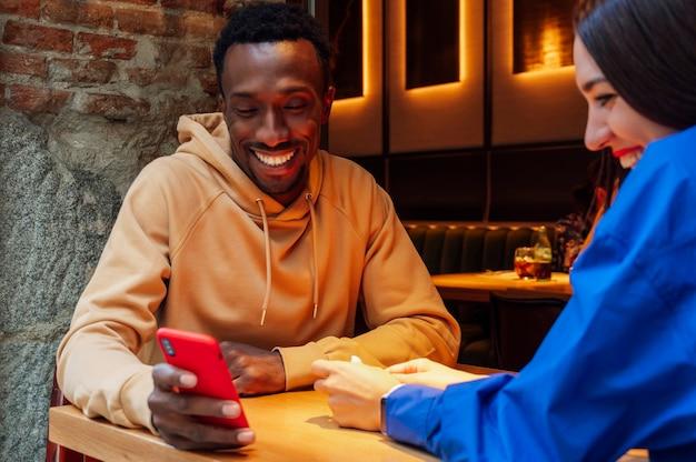コーヒーショップで携帯電話を見ているカップル