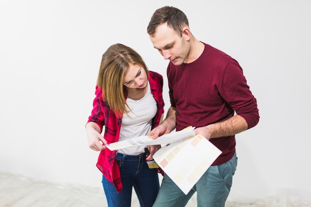 Couple looking at paper with paint samples