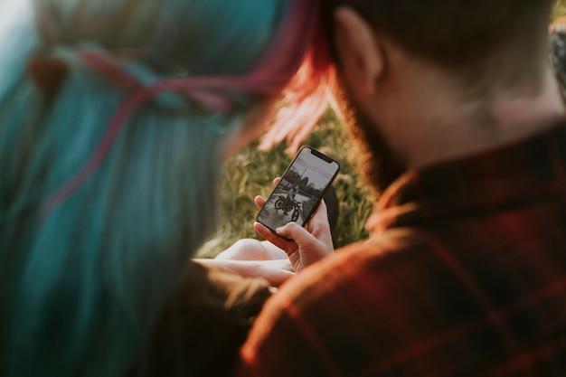 電話の画面を見ているカップル