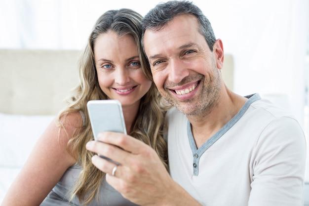 寝室でスマートフォンを見ているカップル