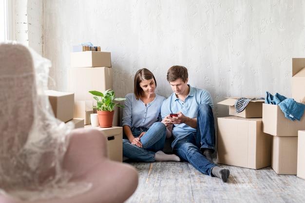 Пара смотрит на смартфон во время упаковки, чтобы переехать