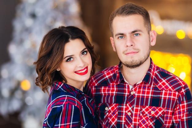 Пара смотрит в объектив камеры на фоне размытой елки и камина
